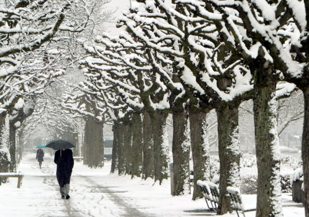 A passerby walks through the snow in Zurich, Switzerland, on Thursday.